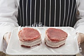 Person holding two bacon-wrapped beef medallions on tray