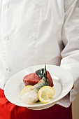 Chef holding beef fillet, king prawn and lemon on plate
