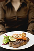 Woman holding plate of Surf & Turf (beef steak with prawn)