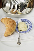 Croissant beside plate of butter with knife