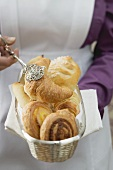 Chambermaid serving breakfast pastries from bread basket