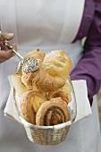 Zimmermädchen serviert Frühstücksgebäck im Brotkorb