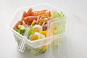 Iceberg lettuce, ham, cheese, egg & vegetables in plastic bowl