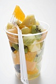 Fruit salad in a plastic beaker with a fork