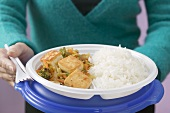 Woman holding tofu,  vegetables and rice on plastic plate
