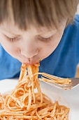 Small boy eating noodles with tomatoes