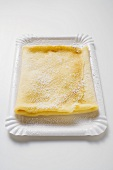 Crêpe with icing sugar on paper plate
