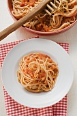 Spaghetti with tomato sauce on plate and in dish