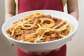 Woman holding bowl of macaroni with mince sauce
