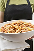 Person holding bowl of macaroni with mince sauce