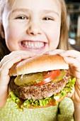 Girl holding large hamburger