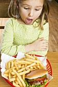 Horrified girl looking at hamburger and chips