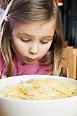 Girl looking sadly at cooked spaghetti