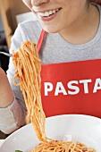 Junge Frau mit Schürze isst Spaghetti mit Tomatensauce
