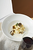 Ribbon pasta with ceps and cream sauce, glass of red wine