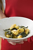 Hand holding plate of gnocchi in sage butter
