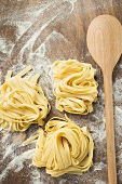 Home-made ribbon pasta beside wooden spoon
