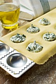 Making ravioli with spinach and soft cheese filling
