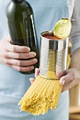 Woman holding spaghetti, tin of tomatoes & bottle of wine