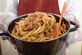 Person serving macaroni with mince sauce from pan