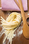 Home-made ribbon pasta, wooden spoons and tea towel