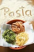Home-made ribbon pasta and the word 'Pasta'