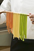 Home-made ribbon pasta hanging over wooden spoon