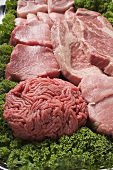 Various types of meat surrounded by parsley