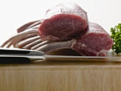 Racks of lamb on chopping board with knife