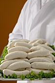 Person holding tray of Weisswurst (white sausages)