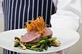 Chef serving beef fillet with green asparagus