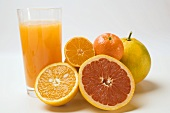 Glass of fruit juice and fresh citrus fruit