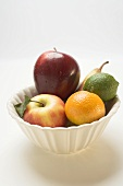 Core fruit and citrus fruit in white bowl