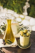 Olives, olive oil, cheese & crackers on table out of doors