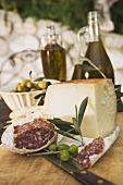 Cheese, salami, olives and olive oil on table out of doors