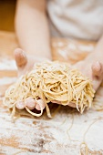 Child's hands holding home-made linguine