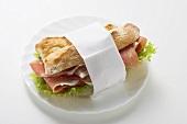 Raw ham sandwich in paper napkin on plate