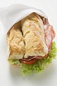 Sausage, tomato and lettuce sandwich in paper napkin