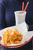 Woman holding basket of crisps and cola in plastic cup
