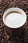 Cup of coffee with milk froth on coffee beans