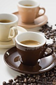Three cups of espresso, coffee beans
