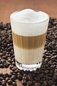 Latte macchiato in glass on coffee beans