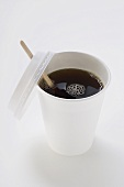 Black coffee in paper cup with wooden stirrer