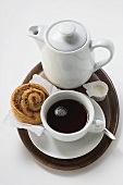 Cup of coffee, cinnamon bun, cream and coffee pot on tray