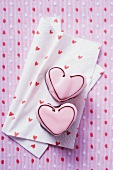 Two pink heart-shaped petit fours on paper napkin