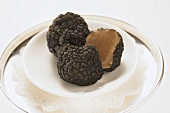 Black truffles, whole and halved, on plate