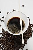 Schwarzer Kaffee im Plastikbecher zwischen Kaffebohnen
