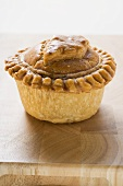 Meat pie on wooden surface