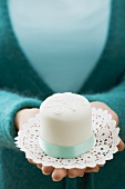 Woman holding a small white cake on a doily