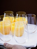 Several glasses of orange juice and empty glasses on tray